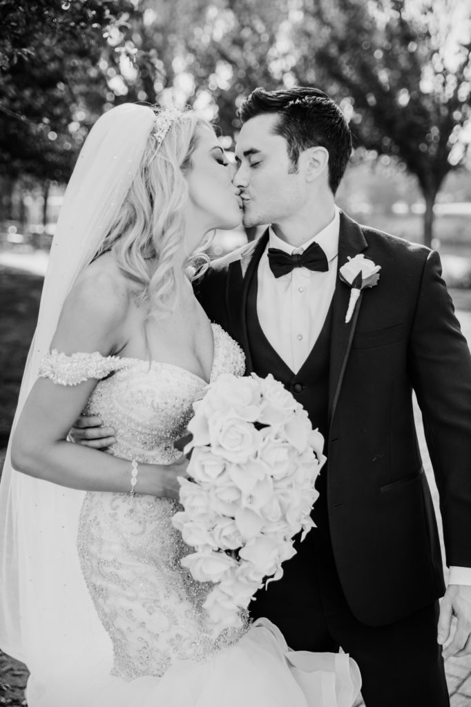 black and white photography groom bride kissing